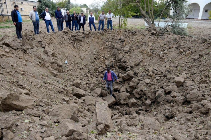 A man inspects a crater which locals said was caused by an Armenian rocket strike in the town of Beylagan on Oct. 4, 2020, during the ongoing fighting between Armenia and Azerbaijan. Azerbaijan said Sunday that Armenian armed forces had shelled its second city of Ganja in a major new escalation of the conflict in the South Caucasus. AFP