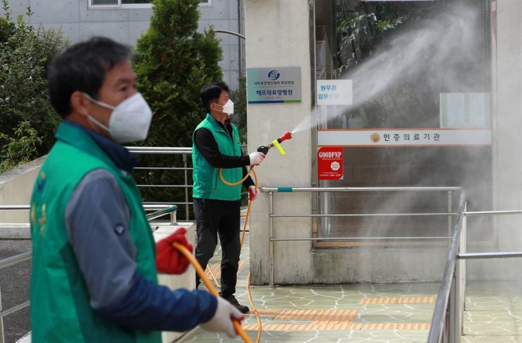 Health officials disinfect a geriatric hospital in Busan, Wednesday, after more than 50 COVID-19 infections were reported there. / Yonhap