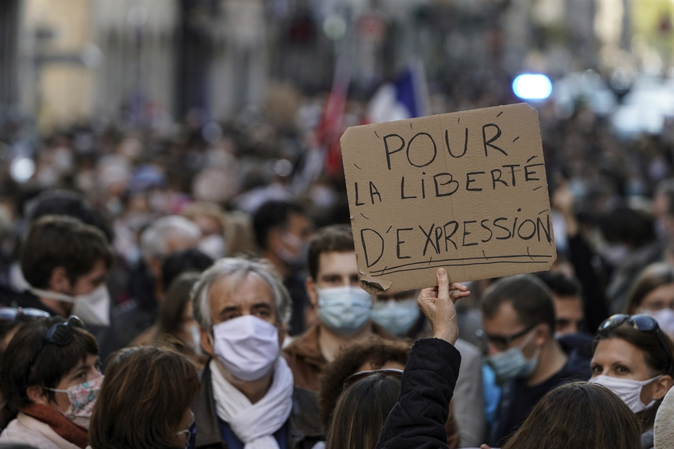 People hold a large banner that reads: 'Don't touch my teacher,' in front of the crowd in Lyon, central France, Sunday, Oct. 18, 2020. Demonstrators in France took part in gatherings in support of freedom of speech and in tribute to a history teacher who was beheaded near Paris after discussing caricatures of Islam's Prophet Muhammad with his class. AP