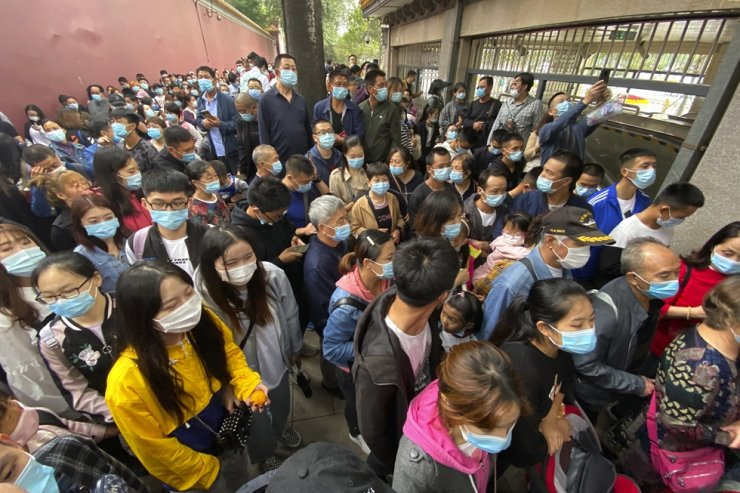 Tourists wearing masks to protect from the coronavirus line up for security checks before visiting the Tiananmen Square area in Beijing, Oct. 1. / AP-Yonhap