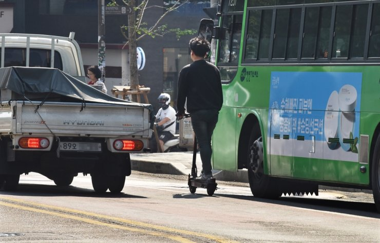 A man rides an electric scooter on a road in Seoul in this 2019 file photo. / Korea Times file
