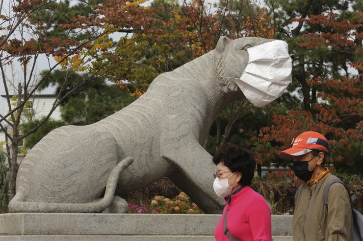 People wearing face masks to help protect against the spread of the coronavirus pass by a statue with a face mask at a park in Seoul, Friday, Oct. 16, 2020. AP