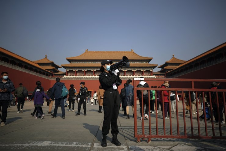 A security guard uses a loud speaker to tell tourists to scan their health code before entering Forbidden City in Beijing, Sunday, Oct. 25, 2020. China's top security authority said Monday that it would crack down on mobile browsers. AP