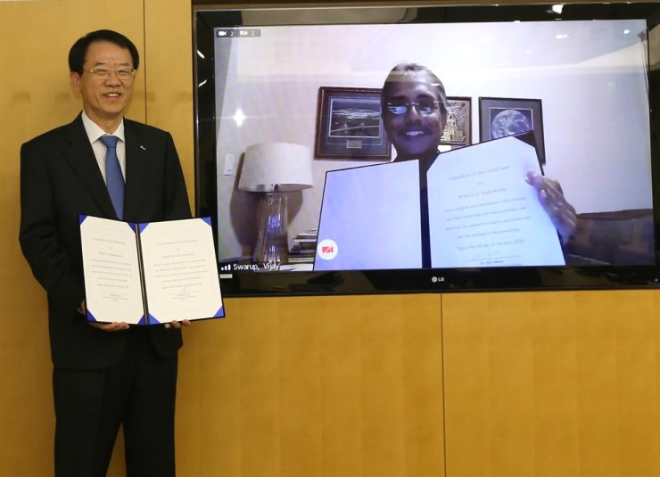 POSCO Technical Research Laboratories head Lee Duk-lak, left, poses with ExxonMobil Research Engineering Vice President Vijay Swarup, on screen, during an online ceremony for the two sides' partnership, Wednesday. Courtesy of POSCO