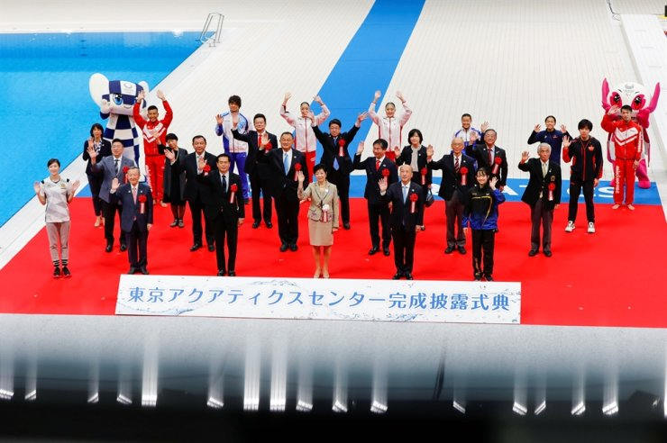 Tokyo's Governor Yuriko Koike, along with other officials and athletes, waves during the Oct. 24 opening ceremony of the Tokyo Aquatics Centre, which will host artistic swimming, diving, and swimming events at the Tokyo Olympic and Paralympic games, as the COVID-19 pandemic continues. Reuters-Yonhap