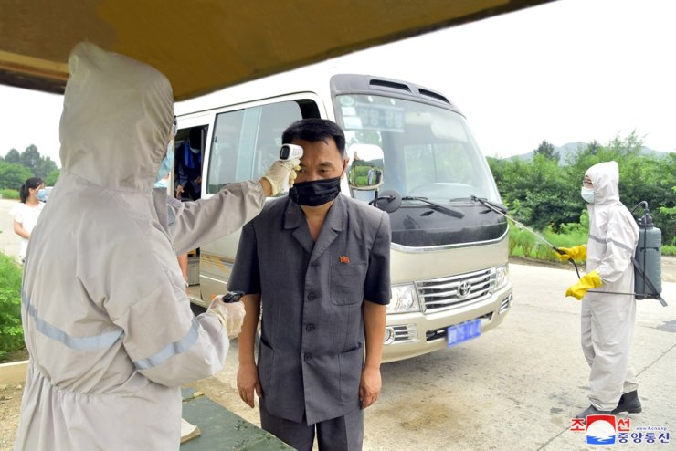 A quarantine official measures a bus driver's temperature with an infrared thermometer in Pyongyang amid the regime's strengthened anti-COVID-19 efforts, Sept. 7. / Yonhap