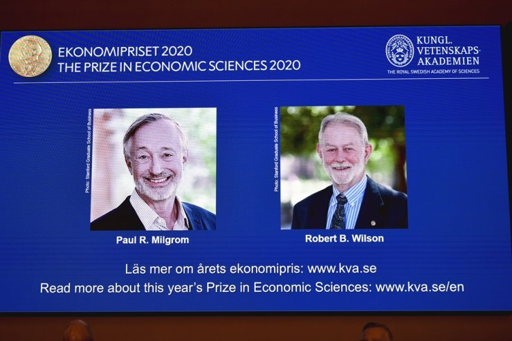 A screen shows pictures of Paul R. Milgrom, left, and Robert B. Wilson, the winners of the Sveriges Riksbank Prize in Economic Sciences in Memory of Alfred Nobel for 2020, at a press conference in Stockholm, Monday. AP-Yonhap