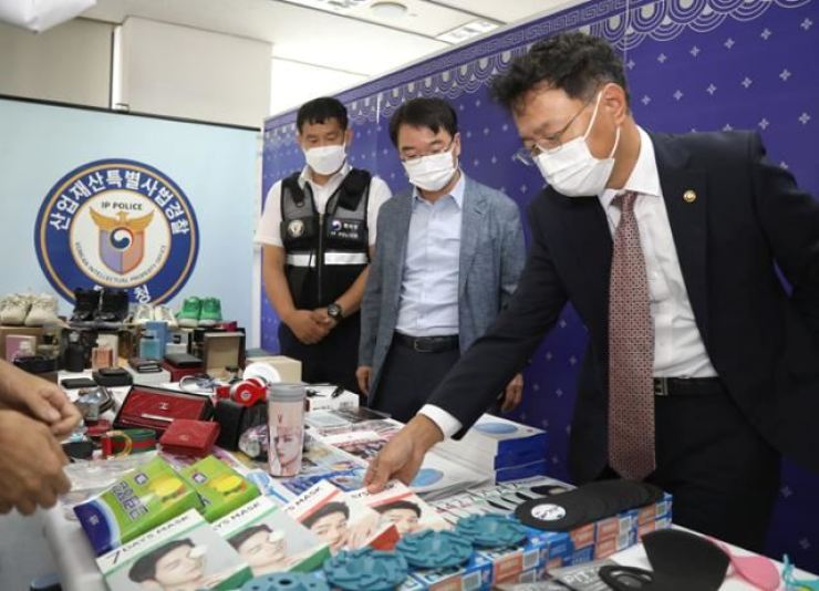 Kim Yong-rae, the commissioner of the Korean Intellectual Property Office (KIPO) examines counterfeit products seized by the Special Judicial Police under KIPO at the Government Complex in Daejeon in this Sept. 15 photo. / Courtesy of Korean Intellectual Property Office