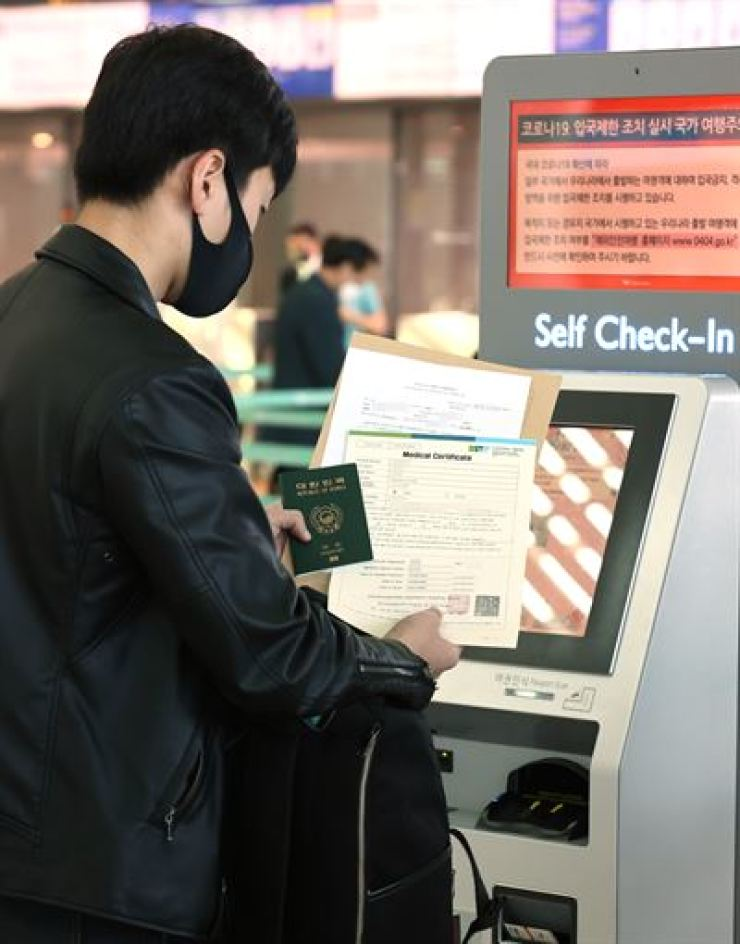A South Korean citizen headed to Japan self-checks at Incheon International Airport, Thursday, with documents including a medical certificate that proves him tested negative on COVID-19 examination. An agreement between South Korean and Japan to exempt visitors to both countries with business purposes from a 14-day self-quarantine begins Thursday. Yonhap