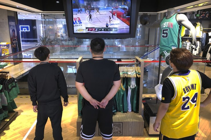 Employees watch a live broadcast of Game 5 of the NBA Finals at an NBA store in Beijing, Saturday, Oct. 10, 2020. AP