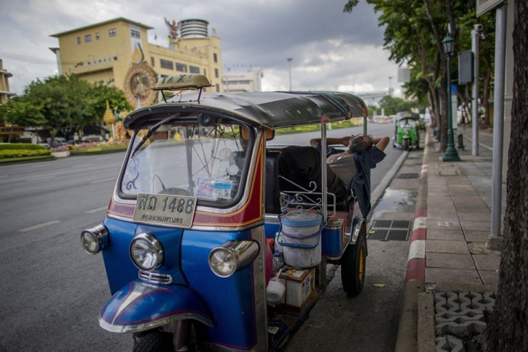 A tuk-tuk taxi driver takes an afternoon nap in his vehicle in Bangkok, Thursday, Oct. 1, 2020. A Thai island hotel will go into mediation with an American guest who faces up to five years in jail after it filed a criminal complaint against him over negative online reviews. AP