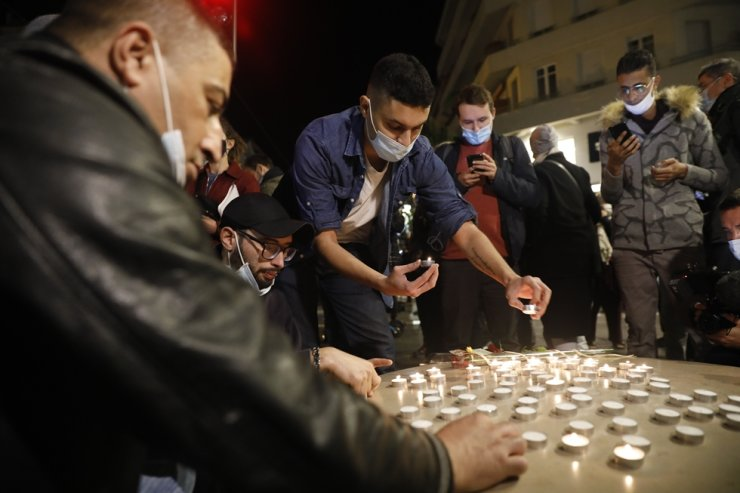 Young people light candles near the entrance of the Notre Dame Basilica church in Nice, France, 29 October 2020, following a knife attack. EPA-Yonhap