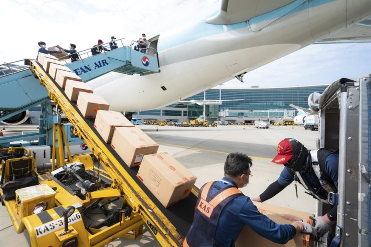 Korean Air employees load a passenger plane with cargo. The national flag carrier is expected to be the only airline here to report an operating profit during the third quarter on the back of its move to cargo transport. / Courtesy of Korean Air