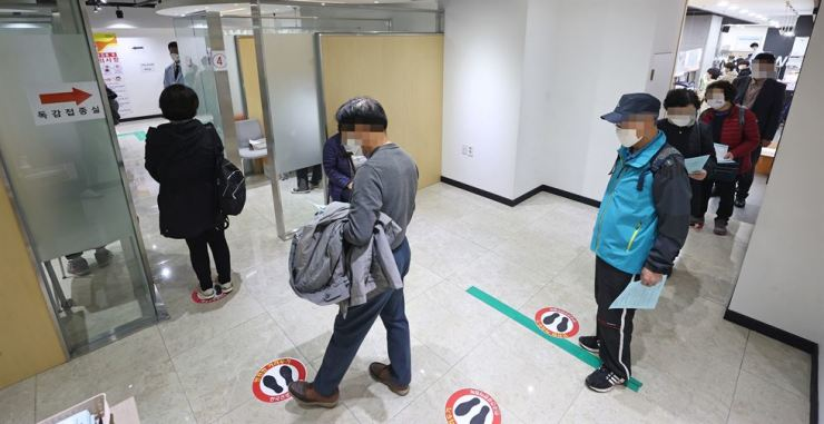 People wait to receive flu shots at a medical center in Seoul, Monday, with free vaccinations available to people between the ages of 62 to 69. Yonhap