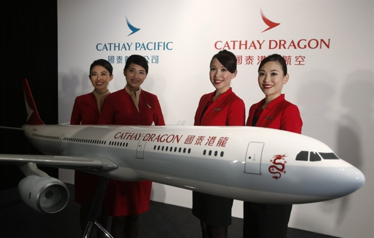 In this Jan. 28, 2016, file photo, flight attendants pose next to a model jet of Hong Kong airline Cathay Dragon, formerly known as Dragonair in Hong Kong. Hong Kong airline Cathay Pacific Airways on Oct. 21, 2020, said it would cut 8,500 jobs and shut down Cathay Dragon in a corporate restructuring, as it grapples with the plunge in air travel due to the pandemic. AP