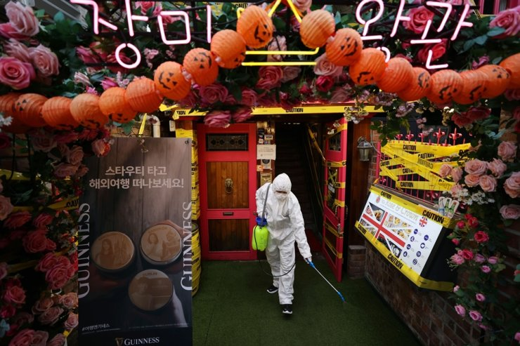 Residents of Itaewon in Seoul's Yongsan District on Oct. 29 disinfect the popular night-out district's venues as Halloween approaches on Oct. 31. Yonhap