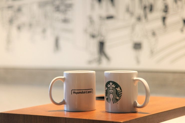 Mugs are decorated with logos of Hyundai Card and Starbucks Coffee at the coffeehouse chain's The Jongno R branch in Seoul in this file photo. / Courtesy of Starbucks Coffee Korea