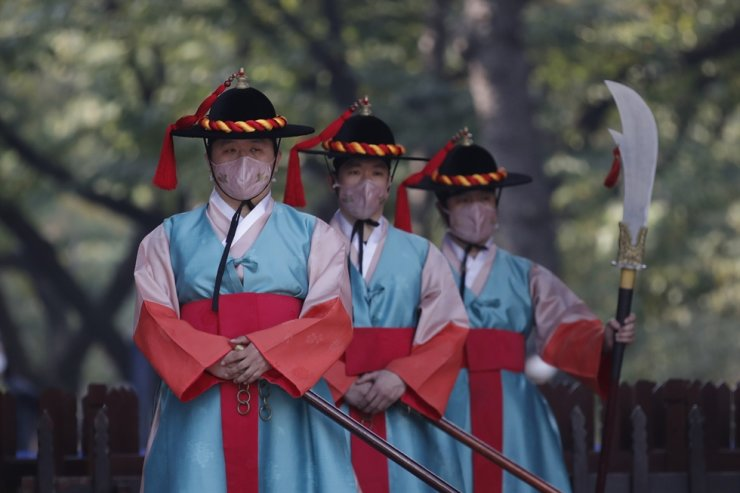 Performers wearing traditional guard uniforms and protective face masks as a precaution against the coronavirus, stand during a re-enactment ceremony of the changing of the Royal Guards, in front of the main gate of the Deoksu Palace in Seoul, Tuesday, Oct. 20, 2020. AP
