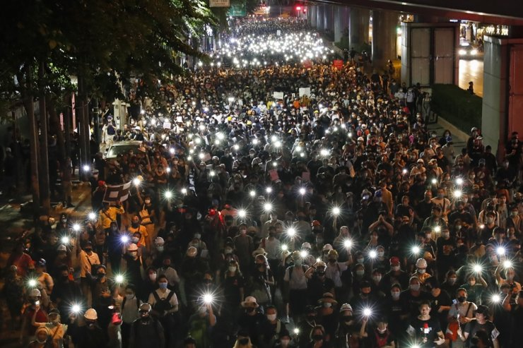Pro-democracy demonstrators shine their mobile phone lights as they march to the German Embassy in central Bangkok, Monday, Oct. 26, 2020. AP