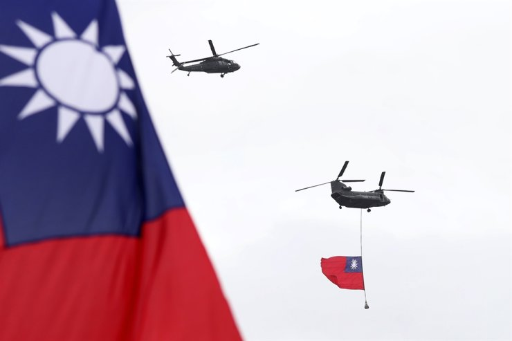 Helicopters fly over President Office with Taiwan National flag during the National Day celebrations in Taipei, Taiwan, Saturday, Oct. 10, 2020. AP