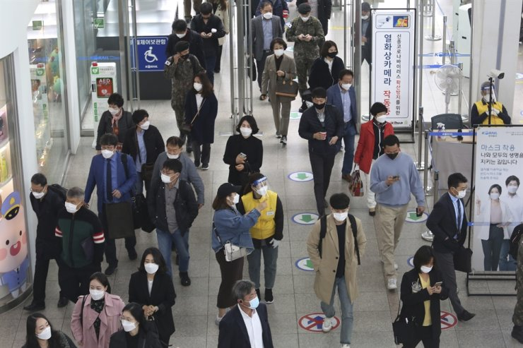 An employee, center right, wearing a face mask and face shield, guides a passenger at the Seoul Railway Station in Seoul, Thursday, Oct. 22, 2020. AP