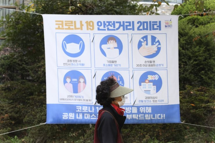 A woman wearing a face mask to help curb the spread of the coronavirus walks by a social distancing sign at a park in Seoul, Friday, Oct. 16, 2020. AP