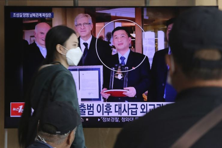 People watch a TV showing an image of Jo Song-gil, the North Korea's former ambassador to Italy, right, during a news program at the Seoul Railway Station in Seoul, South Korea, Wednesday. AP-Yonhap
