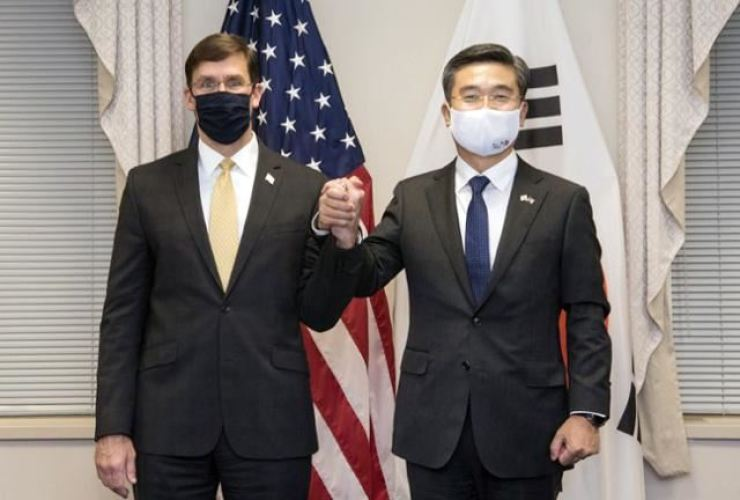 Defense Minister Suh Wook, right, holds hands with U.S. Defense Secretary Mark Esper during the Security Consultative Meeting in Washington, D.C., Oct. 14. / Korea Times file