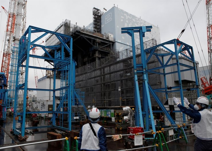 Workers stand near the No.2 reactor building at Tokyo Electric Power Co's tsunami-crippled Fukushima Daiichi nuclear power plant in Okuma town, Fukushima prefecture, Japan January 15, 2020. REUTERS-Yonhap