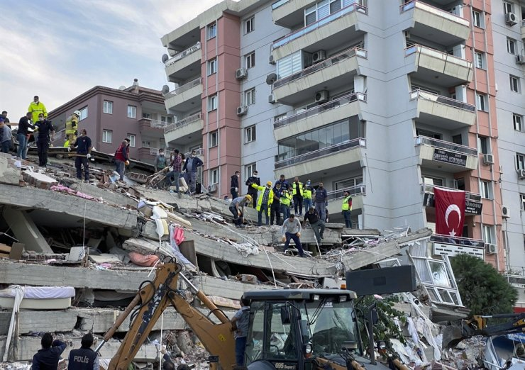 Rescue workers try to save people trapped in the debris of a building, in Izmir, Turkey, Friday, after a strong earthquake struck in the Aegean Sea between the Turkish coast and the Greek island of Samos, killing several people and injuring hundreds amid collapsed buildings and flooding. AP