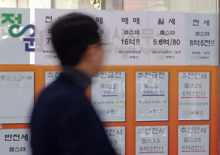 A man walks past a realtor's office in this file photo. / Korea Times file