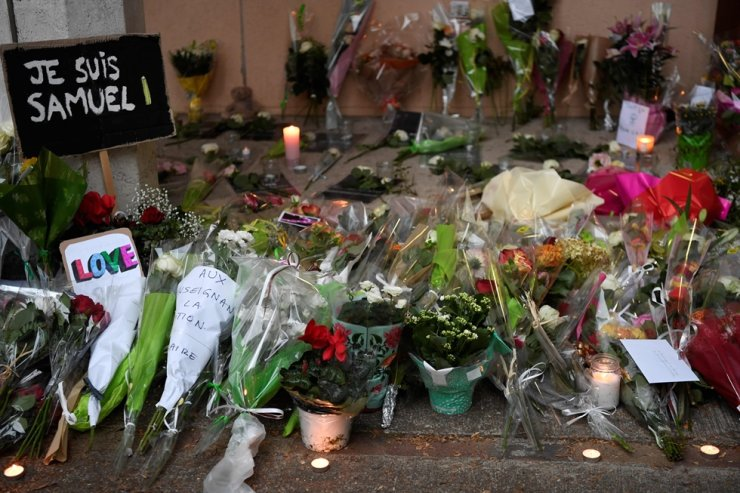 A photo shows flowers, candles and a placard reading 'I am Samuel' at the entrance of a middle school in Conflans-Sainte-Honorine, near Paris, on Oct. 17, 2020, after a teacher was decapitated by an attacker who has been shot dead by police officers. AFP