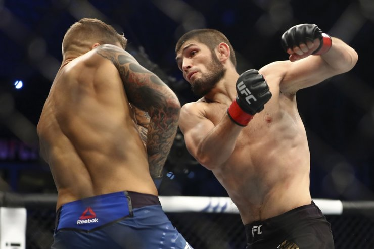 In this Sept. 7, 2019, file photo, Russia's Khabib Nurmagomedov, right, fights with Dustin Poirier during a lightweight title mixed martial arts bout at UFC 242 in Yas Mall in Abu Dhabi, United Arab Emirates. Nurmagomedov, the unbeaten (29-0) UFC lightweight champion, announced his retirement from the sport on Saturday. AP