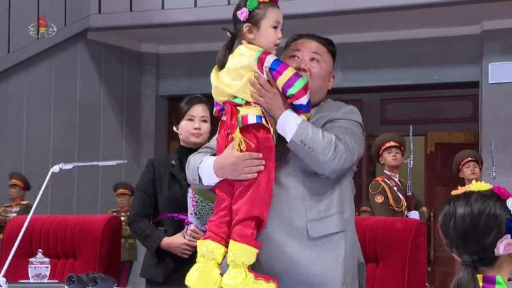North Korean leader Kim Jong-un embraces a child during a performance to mark the 75th anniversary of the Workers' Party of Korea, Oct. 12. Yonhap