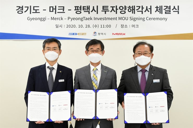 Kim Woo-kyu, center, managing director of Merck Korea, poses with Gyeonggi Province Vice Governor Lee Yong-chul, left, and Pyeongtaek City Vice Mayor Lee Jong-ho, during a memorandum of understanding ceremony at the company's Advanced Technology Center in Pyeongtaek, Gyeonggi Province, Wednesday. / Courtesy of Merck Korea