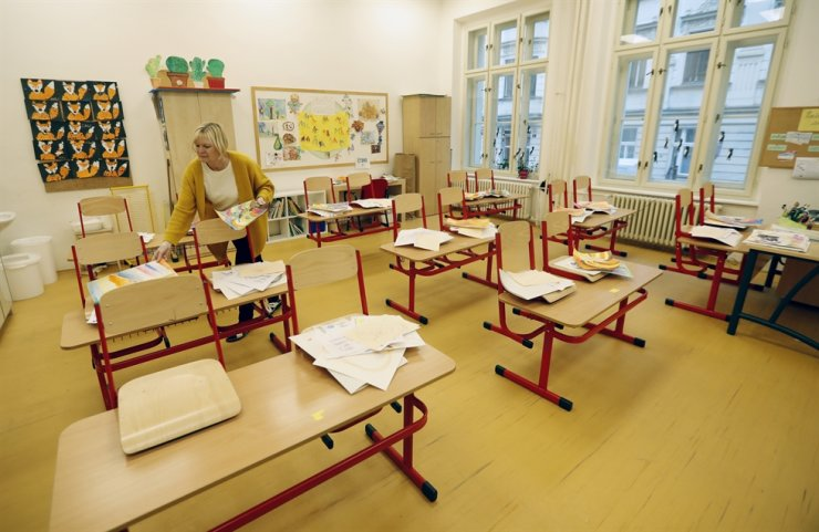 A teacher sorts drawings in an empty classroom at a closed school in Prague, Czech Republic, Wednesday. Amid widespread efforts to curb the new wave of coronavirus infections in one of the hardest hit European countries, the Czech Republic closed again all its schools. AP-Yonhap
