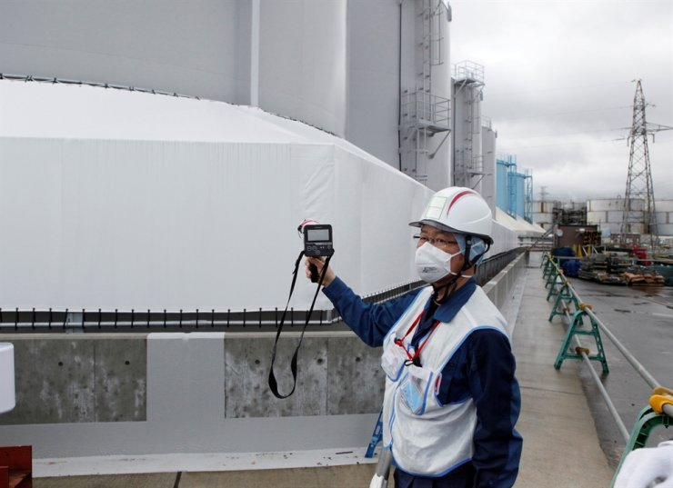An employee of Tokyo Electric Power Co (TEPCO) uses a Geiger counter next to storage tanks for radioactive water at TEPCO's tsunami-crippled Fukushima Daiichi nuclear power plant in Okuma town, Fukushima prefecture, Japan, Jan. 15, 2020. Reuters
