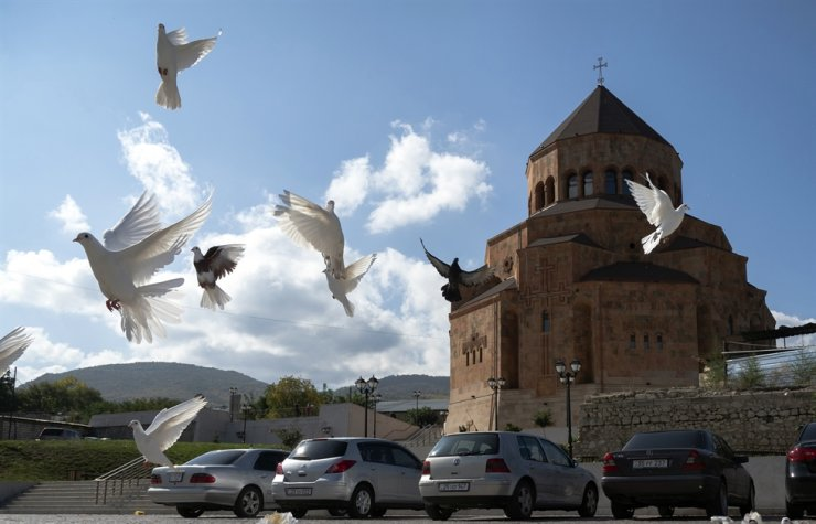 Pigeons fly near the Holy Mother of God Cathedral in Stepanakert during a military conflict in the separatist region of Nagorno-Karabakh, Friday. Armenia and Azerbaijan say they have agreed to a ceasefire in the enclave starting noon Saturday. AP