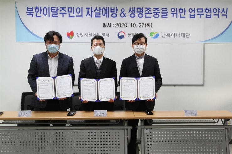 From left, Korea Suicide Prevention Center (KSPC) Director Paik Jong-woo, Settlement Support Center for North Korean Refugees Director Lee Joo-tae and Korea Hana Foundation President Jung In-sung pose with written agreements on cooperation in developing suicide prevention programs for North Korean defectors, at the KSPC, Seoul, Tuesday. / Courtesy of Ministry of Unification