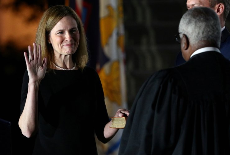 Amy Coney Barrett holds her hand on the Holy Bible as she is sworn in as an associate justice of the U.S. Supreme Court by Supreme Court Justice Clarence Thomas on the South Lawn of the White House in Washington, U.S., Oct. 26, 2020. Reuters