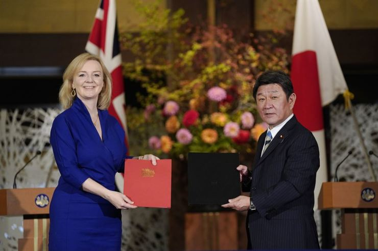 British International Trade Secretary Liz Truss, left, and Japanese Foreign Minister Toshimitsu Motegi exchange agreement documents for economic partnership between Japan and Britain at Iikura Annex of the Foreign Ministry in Tokyo, Friday. Japan and Britain signed a bilateral free trade deal Friday in the the first such major post-Brexit deal, reducing tariffs on Yorkshire lamb sold in Japan, as well as auto parts for Japan's Nissan plant. AP-Yonhap