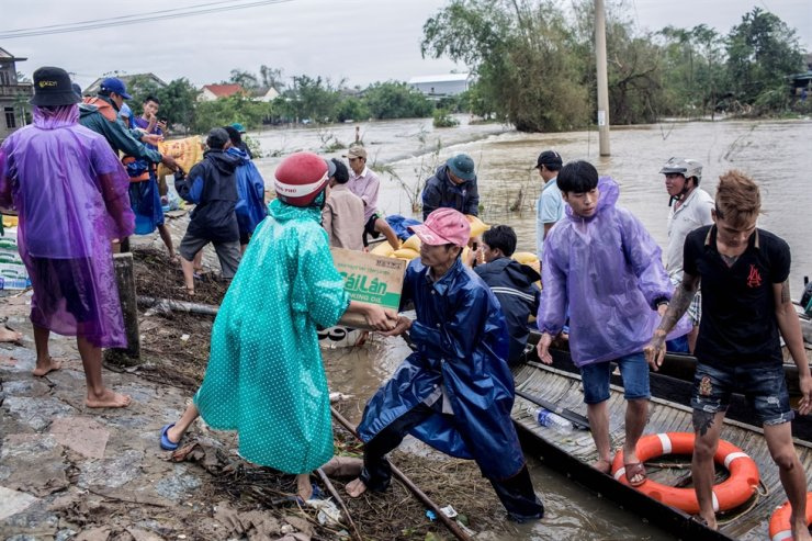 Local residents and volunteers deliver aid packages to residents affected by heavy flood in Quang An Commune, Thua Thien Hue, Vietnam, Oct. 20, 2020. Handout via Reuters