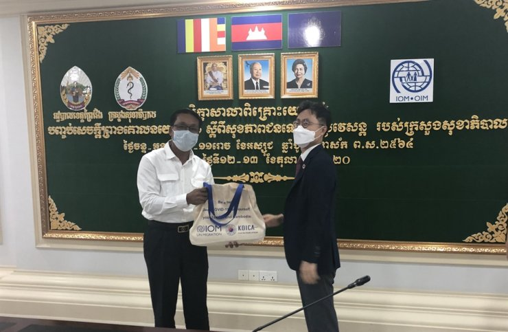 Roh Hyun-jun, right, country director of the Korea International Cooperation Agency (KOICA) in Cambodia, delivers a bag of food and hygiene products to a Cambodian official during a ceremony, Oct. 14, in the Cambodian province of Prey Veng. KOICA is supplying 15,000 sets of food and hygiene products until December for Cambodians who had migrated to neighboring countries but returned home after their livelihoods were hit by the COVID-19 pandemic. / Courtesy of KOICA