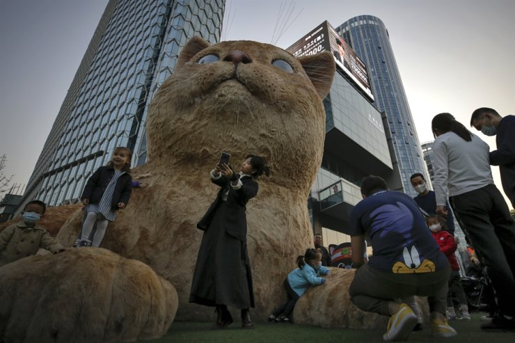 A woman takes a selfie as visitors wearing face masks gather near a giant cat structure on display at a commercial office building in Beijing, Sunday, Oct. 18, 2020. AP