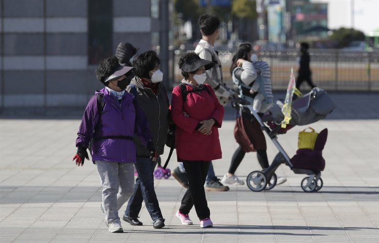 Visitors wearing face masks as a precaution against the coronavirus, walk at a park in Seoul, Saturday, Oct. 24, 2020. AP
