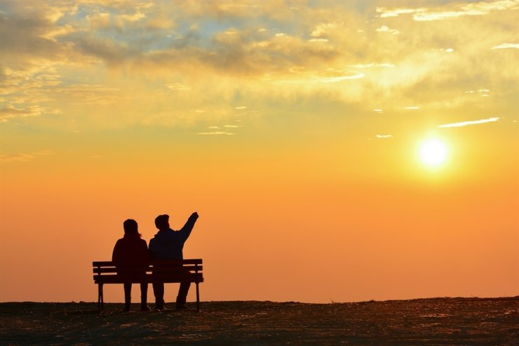 A man and woman sit on a bench, watching the sunset. The majority of Korean travelers think 'who you travel with' is more important than 'where you go,' according to a study from global online travel agency Expedia. / Courtesy of Expedia