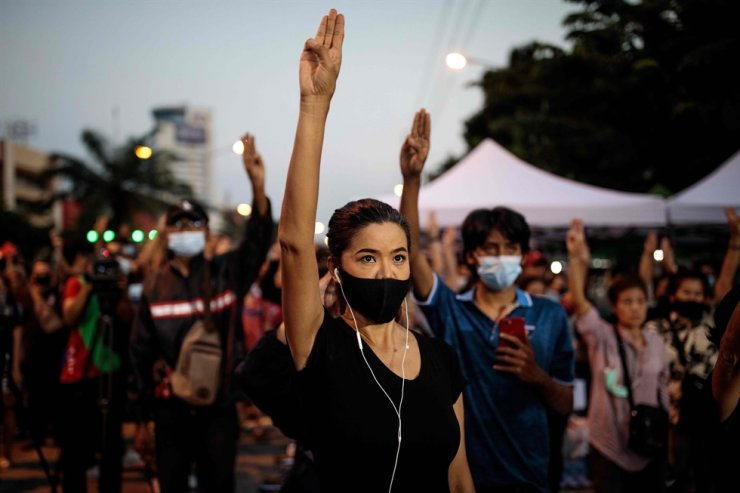 Pro-democracy protesters hold up the three-finger salute outside Bangkok Remand Prison in Bangkok on Oct. 24, 2020, as they urge the release of protest leaders and other activists held at the facility following arrests during the ongoing demonstrations. AFP