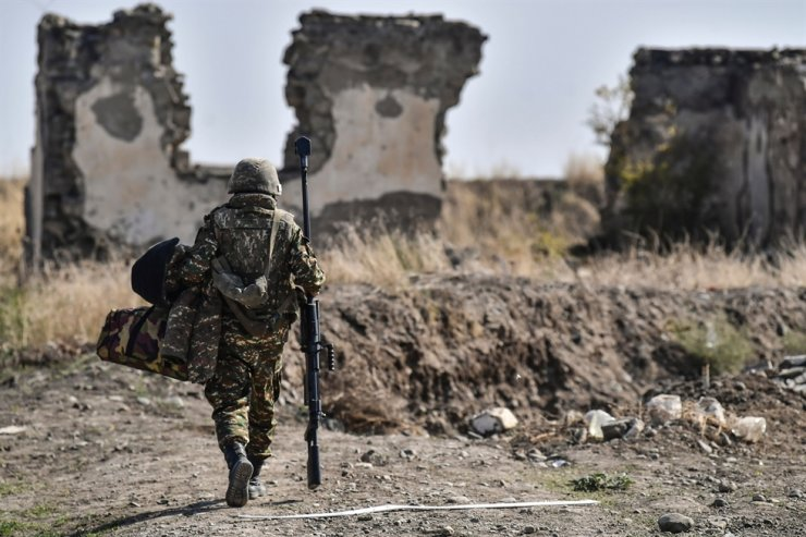 An Armenian soldier carries his machine gun at the front line at troops hold positions on Oct. 18, 2020, during the ongoing fighting between Armenia and Azerbaijan. AFP