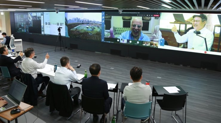 SK Engineering & Construction CEO Ahn Jae-hyun, right on screen, gestures during an online meeting with Veea CEO Allen Salmasi, left on screen, to sign an MOU for the two companies' partnership in this photo provided on Wednesday. Courtesy of SK E&C