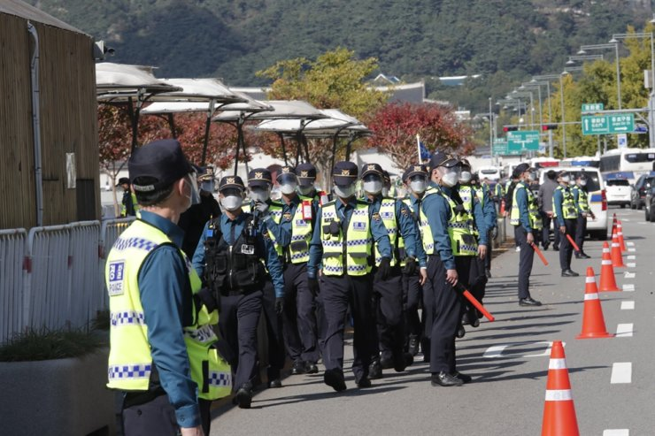 Police officers wearing face masks patrol to block protesters' possible rallies against the government in Seoul, Friday, Oct. 9, 2020. AP